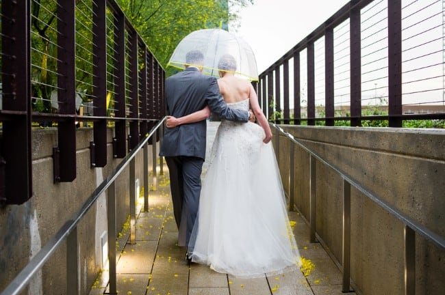 newlyweds walking under clear umbrella