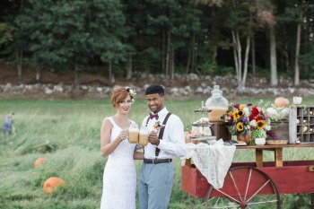 pumpkin styled shoot couple cheers in front of vintage cart