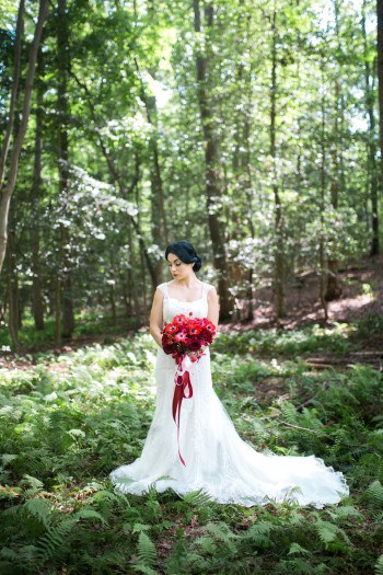 bride-in-forest-with-red-bouquet