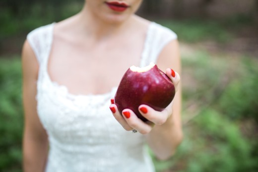 bride-in-white-gown-holds-red-apple-with-a-bite-taken-out