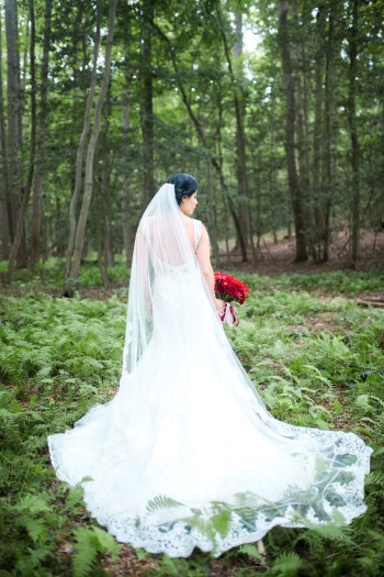 bride-wearing-cathedral-length-veil-in-a-forest