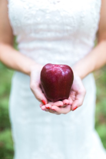 close-up-of-snow-white-styled-bride-holding-a-red-apple