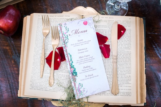 menu-card-cutlery-and-red-rose-petals-on-old-book