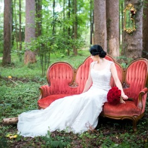 snow-white-bride-on-red-chaise-lounge-in-forest