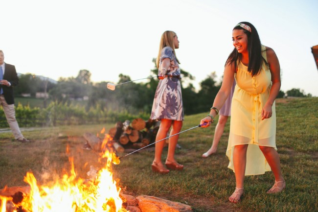 bridesmaid roasting marshmellow over fire