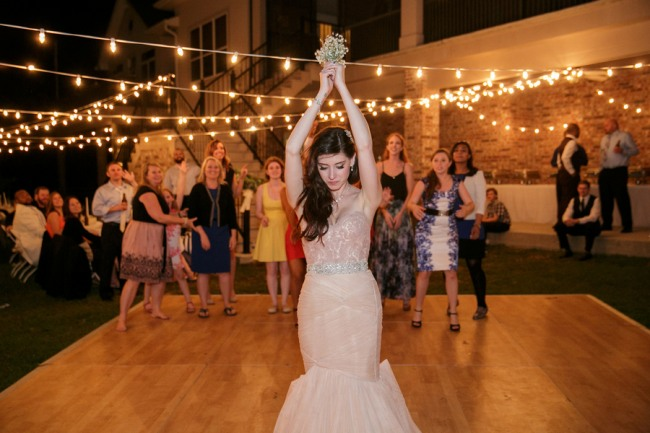 string lights overhead as bride tosses bouquet
