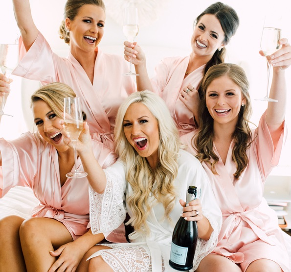 bridesmaids in silk robes celebrate with champagne