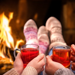 couple hold two hot drinks near fireplace