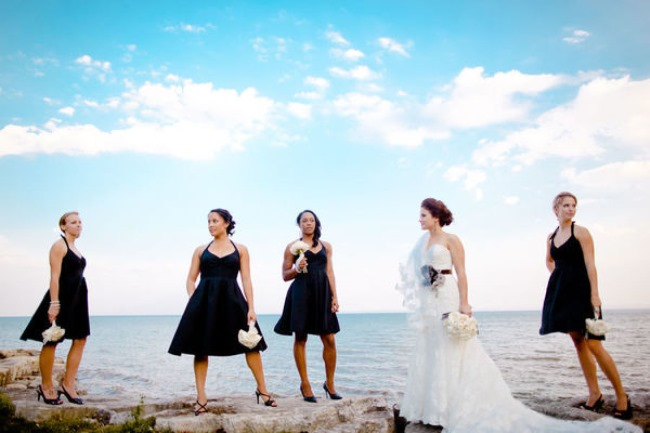 bride with bridesmaids in black stand on cliff shore