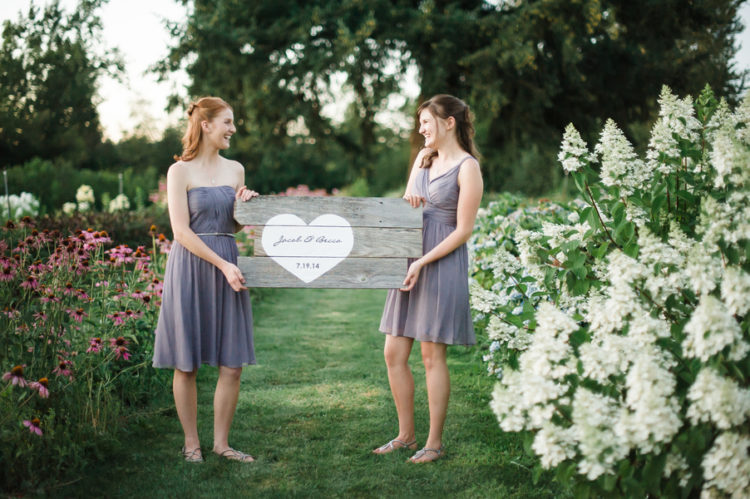 two bridesmaids in lavender dresses hold a wood sign