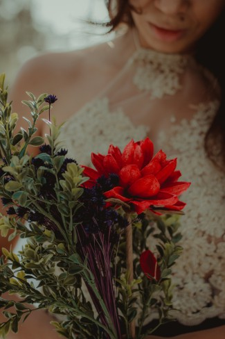 bride holding red flower bouquet