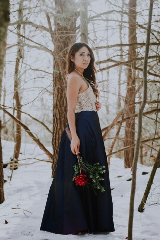 bride in dark blue dress in snow
