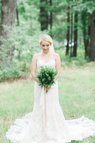 bride in forest holds rosemary bouquet