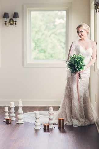 bride leans against window with candles on floor