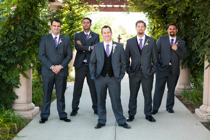 groom-and-groomsmen-stand-under-trelice-dressed-in-purple-neckties