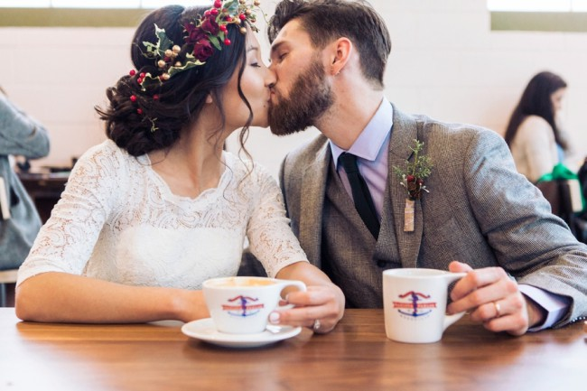 newlyweds kiss at cafe with coffee