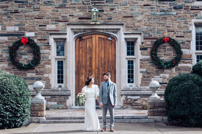 newlyweds stand at front of wood doors