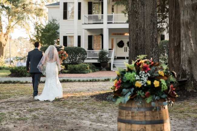 newlyweds walk towards plantation house
