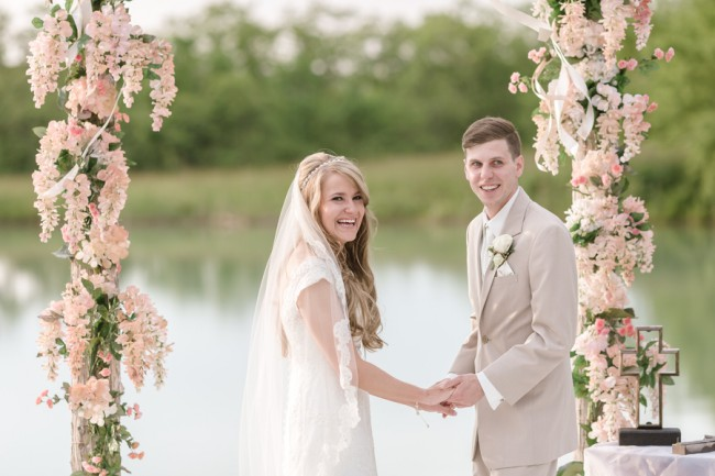newlyweds with floral altar