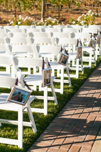 photos as aisle markers hang on white wedding ceremony chairs