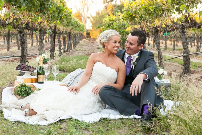 smiling newlyweds picnic in Lorimar Winery vineyard