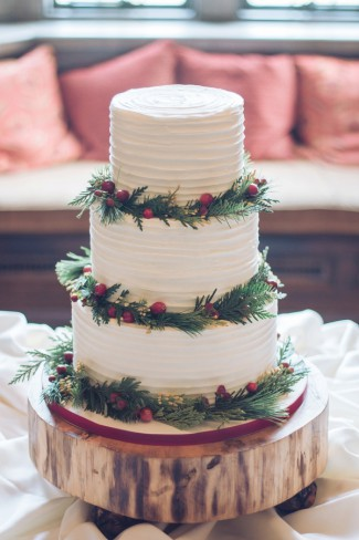 three tier cake with holly berries on wood round