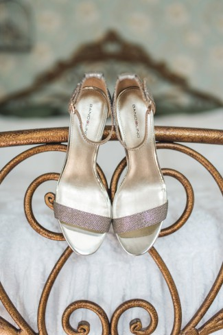 bridal shoes hang from bed