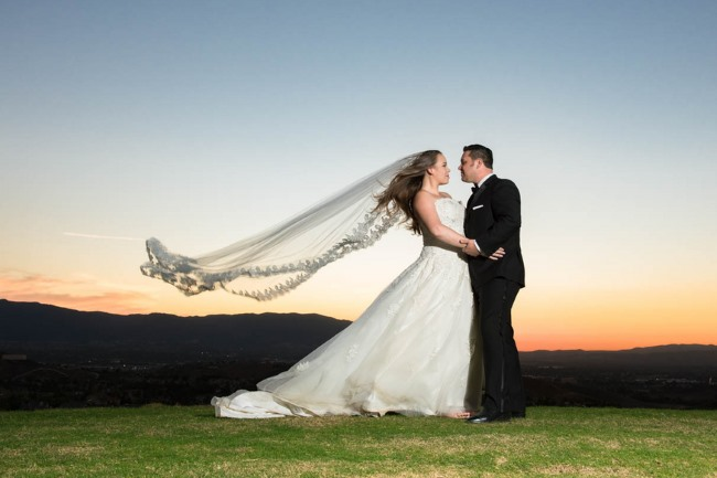 bride with wind swept veil + groom