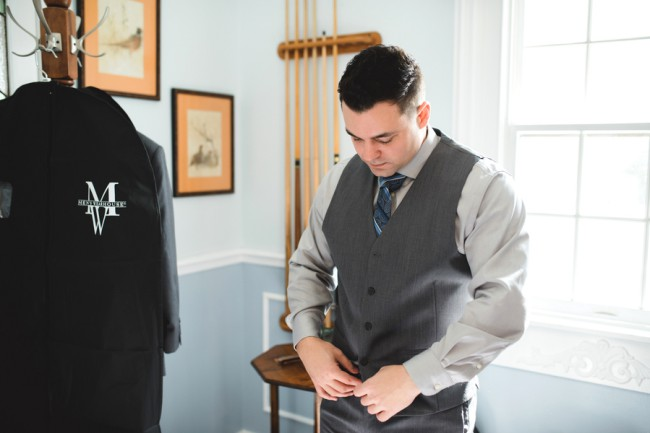 groom in vest getting ready