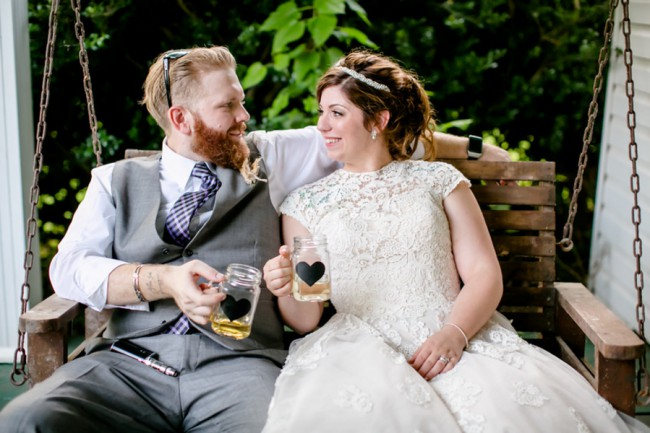 newlyweds sit on swinging porch bench