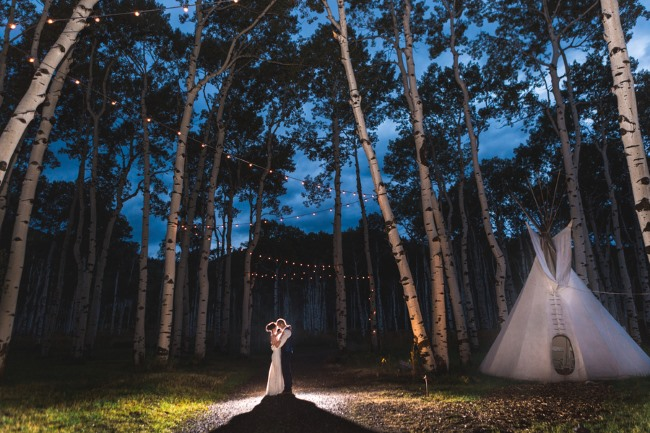 backlit newlyweds next to teepee at night