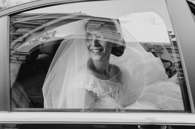 black and white of bride in car