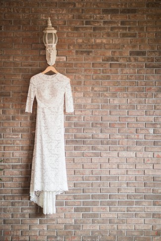bridal dress hanging on brick wall