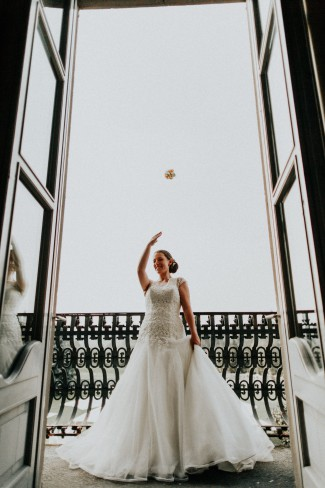 bride throwing bouquet from balcony