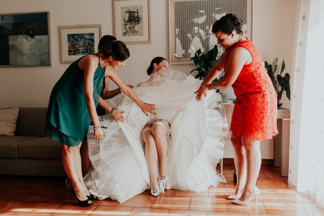 bridesmaids applying garter to bride