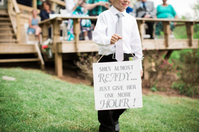 child carrying sign down lawn aisle