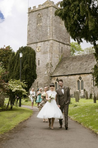 newlyweds in front of old UK church