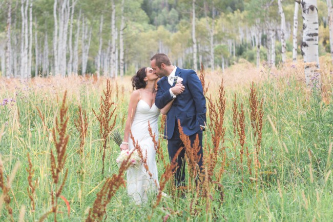 newlyweds kiss in long grass
