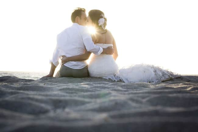 Bbride-and-groom-sitting-on-victoria-beach-in-laguna-head-to-head-while-sun-is-setting
