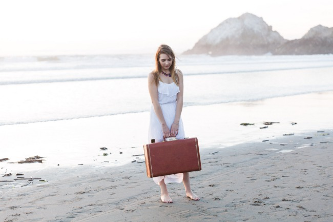 boho beach bride with luggage on beach