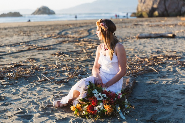 boho bride sitting on California beach