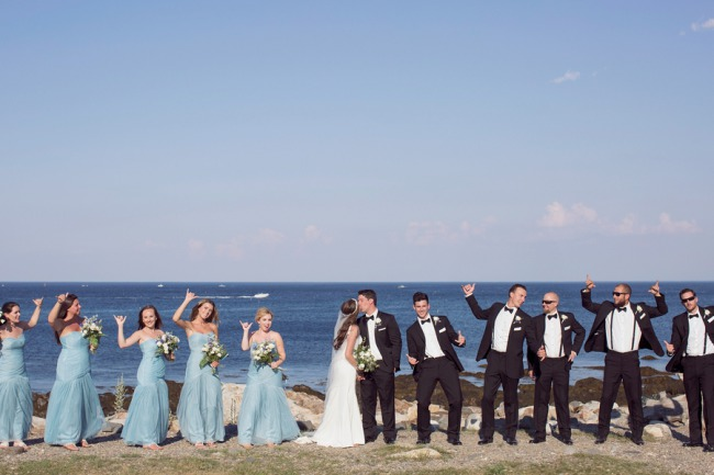 bridal party in a row near sea