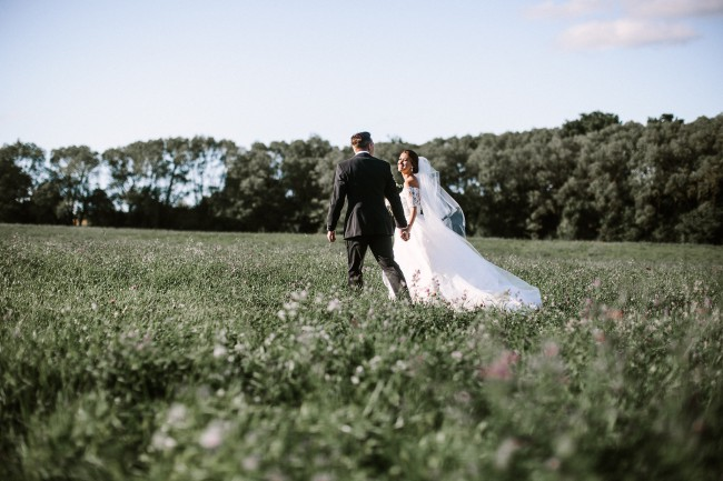 bride and groom walk in field