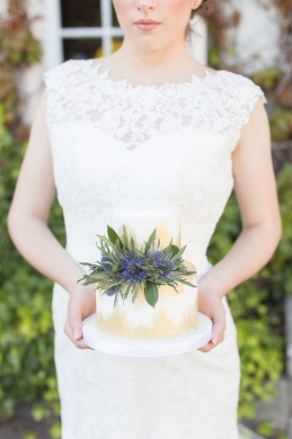 bride holds small cake topped with blue thistle