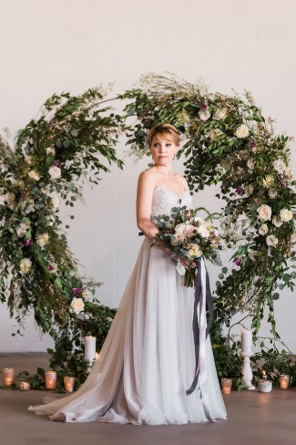 bride with large greenery wreath backdrop