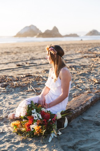bride with bouquet sits on beach wood