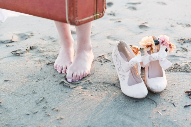 bride's feet with shoes on beach
