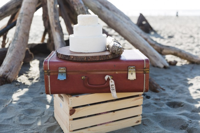 cake atop luggage on beach