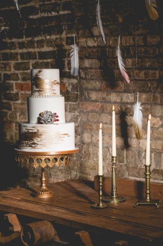 cake on gold platter set against exposed brick