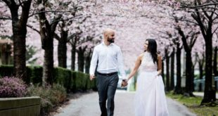 cherry blossom engagement shoot couple walk on Vancouver sidewalk